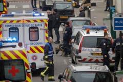 Polizisten und Rettungskräfte vor dem Redaktionsgebäude des Satiremagazins in Paris. (Bild: Keystone)