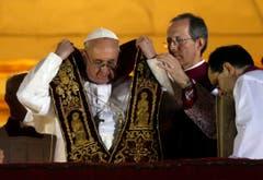 Papst Franziskus zieht die Schärpe an. (Bild: Keystone)
