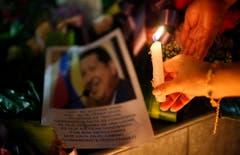 Eine Frau zündet eine Kerze für Hugo Chávez an. (Bild: Keystone)
