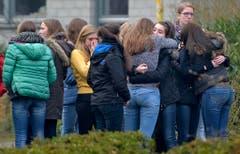 Gymnasiasten versammeln sich vor der Schule, um miteinander zu trauern. (Bild: Keystone)