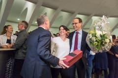 Sven Bradke (FDP) übergibt Marc Mächler ein Geschenk, daneben steht dessen Ehefrau. (Bild: Michel Canonica)