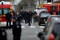 Polizisten und Feuerwehrleute beim Tatort. (Bild: Keystone)