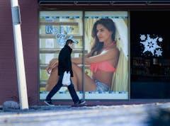 Was für ein Kontrast: Ein Mann hastet in der Kälte an einer Werbung vorbei, die eine leicht bekleidete Dame zeigt. (Bild: Keystone)