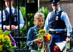Ein Mädchen bringt im Gedenken an den verstorbenen Prinzen Johan Friso Blumen zum Palast Huis ten Bosch. (Bild: Keystone)