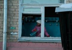 Eine Einwohnerin von Tscheljabinks räumt Glasscherben zusammen. Wegen der enormen Druckwelle des Meteoriten barsten vielerorts Scheiben und wurden Häuser abgedeckt. (Bild: Keystone)