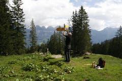Hier wird der zweite Wegweiser montiert. Willi Marthy ist genug gross um sie zu befestigen. Andernfalls würde er sich mit einem Baumstrunk zu helfen wissen. (Bild: Jolanda Riedener)