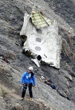 Ein Mann bei einem Wrackteil der Germanwings-Maschine. (Bild: Keystone)