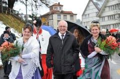 Ein gut gelaunter Hans Altherr auf dem Weg zum Trogener Dorfplatz, flankiert von Trachtenfrauen. (Bild: Keystone)