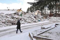 Eine Frau geht an Trümmern vorbei. (Bild: EPA/Emiliano Grillotti)