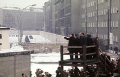 Der amerikanische Praesident Richard Nixon (auf der Aussichtsplattform zweiter von links) besichtigt während seines Berlin-Besuchs am 26. Februar 1969 die Berliner Mauer. (Bild: Keystone)