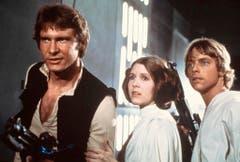 Star Wars ist die kommerziell erfolgreichste Filmserie der Geschichte. Allein bis 2012 wurden inklusive der Kinotickets geschätzte 24 Milliarden Euro eingenommen. Im Bild die drei Hauptdarsteller der ersten drei Teile (v.l.): Harisson Ford als Han Solo, Carrie Fisher als Prinzessin Leia und Mark Hamill als Luke Skywalker. (Bild: Keystone)