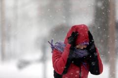Eine Frau versucht sich in St.Louis gegen den Schnee zu schützen. (Bild: Keystone)
