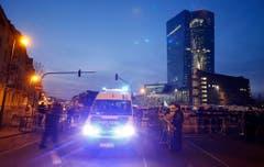 Ein Polizeibus fährt am Morgen früh an Barrikaden vorbei, um sich auf die erwarteten Demonstranten vorzubereiten. Im Hintergrund ist das beleuchtete Gebäude der Europäischen Zentralbank zu sehen. (Bild: Keystone)
