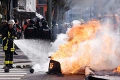 Ein Feuerwehrmann löscht brennende Blockaden. (Bild: Keystone)