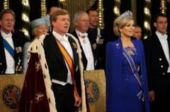König Willem-Alexander mit dem Königsmantel und Königin Maxima im königsblauen Kleid mit Diamantendiadem: Das Königspaar singt die Nationalhymne. (Bild: Keystone)