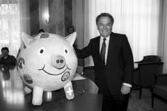 Der Finanzminister Otto Stich mit einem selbstgebastelten, rosa Sparschwein, das er von Auslandschweizerkinder 1994 geschenkt bekam. (Bild: Keystone)