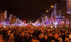 Die Avenue des Champs-Elysées in Paris ist dicht bevölkert in der Silvesternacht. (Bild: Keystone)
