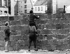 Neugierige Berliner Kinder erhaschen am 23. August 1961 über die frisch errichtete Mauer im Berliner Bezirk Wedding einen Blick nach Ostberlin. (Bild: Keystone)
