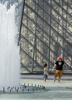 Auch in Paris - hier beim Louvre - ächzte man unter der Hitze. Und war froh um jede Abkühlung. (Bild: THOMAS PADILLA (AP))