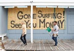 Nun hat der Tropensturm Kurs in Richtung USA genommen. In Ocean City machen zwei Surfshop-Besitzer ihren Laden dicht. (Bild: Keystone)