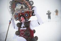 Im Schneegestöber sind die Silvesterchläuse unterwegs. (Bild: Keystone / Gian Ehrenzeller)