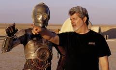 """George Lucas hat als Drehbuchautor auch mehr Geld eingespielt als jeder andere. Rund 3 Milliarden Dollar gaben Kinozuschauer bisher aus, um seine Filme zu sehen. Im Bild mit Roboter C-3PO während den Dreharbeiten zu """"Star Wars II: Attack of the Clones"""". (Bild: LISA TOMASETTI (AP LUCASFILM))"""