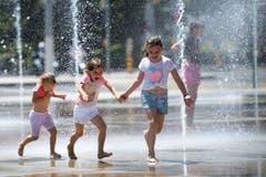Beliebter Sommerplausch für Kinder: Abkühlen bei Wasserfontänen, hier in Genf. (Bild: MARTIAL TREZZINI (KEYSTONE))