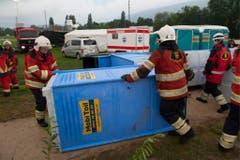 Helfer stellen ein umgekipptes mobiles WC wieder auf. (Bild: Keystone)