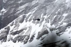 Ein Rettungshelikopter im Einsatz über dem Absturzgebiet. (Bild: Keystone)