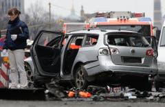 Eine Frau von der Spurensicherung steht neben dem beschädigten Auto. (Bild: Keystone)