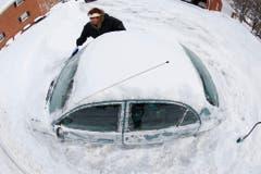 Eine Frau buddelt ihr Auto aus. (Bild: Keystone)