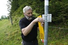 Willi Marthy montiert die Wegweiser, schiebt sie danach hoch und befestigt sie. (Bild: Jolanda Riedener)