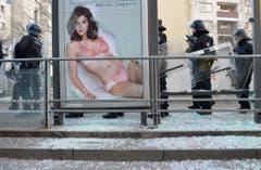 Bei einer Tramhaltestelle liegt Glas eines zerstörten Werbeplakates auf dem Boden. Im Hintergrund stehen Polizisten. (Bild: Keystone)
