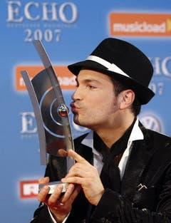 """Der Preisträger in der Kategorie 'Künstler Natinoal Rock/Pop', Roger Cicero, posiert am 25. März 2007 nach der Verleihung der """"Echo"""" Musikpreise in Berlin für die Fotografen. (Bild: Keystone)"""