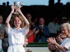 Martina Hingis zeigt am 3. Juli 1994 die Trophäe, die sie soeben von der Herzogin von Kent, rechts, in Empfang nehmen durfte. Das Ausnahmetalent ist die jüngste Gewinnerin des Juniorinnen-Titels in Wimbledon. (Bild: Keystone)