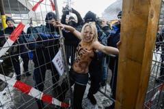 Ein Polizist packt zu - nach Aufnahme der Personalien wurden die Frauen dann wieder entlassen. (Bild: Keystone)
