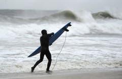 Während mehrere Ortschaften an der Ostküste bereits evakuiert worden sind, geniesst ein Surfer in Long Beach die hohen Wellen. (Bild: Keystone)