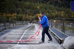 Marcello Crüzer vom Bauamt der Gemeinde Bregaglia öffnet das Absperrband über die Notbrücke, die nach Bondo führt. (Bild: KEYSTONE/Gian Ehrenzeller)