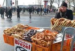 Ein Mann verkauft seine Brezeln inmitten der Demonstranten. (Bild: Keystone)