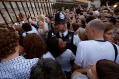 Ein Polizist versucht die Menge vor dem Buckingham Palace unter Kontrolle zu halten. (Bild: Keystone)