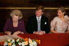 Jetzt ist sie nicht mehr Königin: Beatrix unterschreibt die Abdankungsurkunde. Neben ihr sitzen der neue König Willem-Alexander und Königin Maxima. (Bild: Keystone)