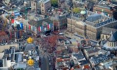 Kronen auf den Gebäuden, eine orangefarbene Menschenmasse auf dem Dam, Flaggen in den Nationalfarben: Die Niederlande feiert den neuen König Willem-Alexander. (Bild: Keystone)