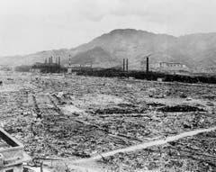 Hier standen früher Industriebauten und kleinere Wohnhäuser. Nach dem Atombombenabwurf sieht man nur noch die Überreste der Mitsubishi Waffenfabrik und ein mit Beton verstärktes Schulgebäude am Bergfuss. (Bild: Keystone)