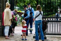 Menschen bringen Blumen zum Palast. (Bild: Keystone)