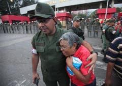 Ein Armeeangehöriger tröstet vor dem Militärspital in Caracas eine Frau. (Bild: Keystone)