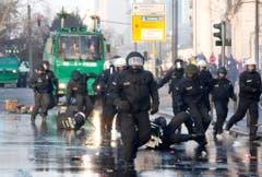 Polizisten jagen Demonstranten, welche das EZB-Hauptgebäude blockieren wollen. (Bild: Keystone)