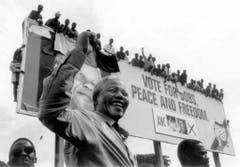ANC-Präsident Nelson Mandela winkt seinen Anhängern im April 1994 im Rahmen der ersten demokratischen Wahlen in Südafrika. Bei den Wahlen gewinnt der ANC die Mehrheit, Mandela wird erster schwarzer Präsident des Landes. (Bild: Keystone)