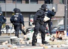 Polizisten räumen Steine weg, welche Demonstranten geworfen haben. (Bild: Keystone)