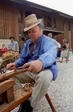 Bundesrat Otto Stich bearbeitet im Juli 1995 in Wolhusen (Luzern) während des Ausflugs des Bundesrats ein Stück Holz. (Bild: Keystone)