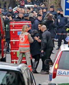 Rettungskräfte helfen einer Frau. (Bild: Keystone)